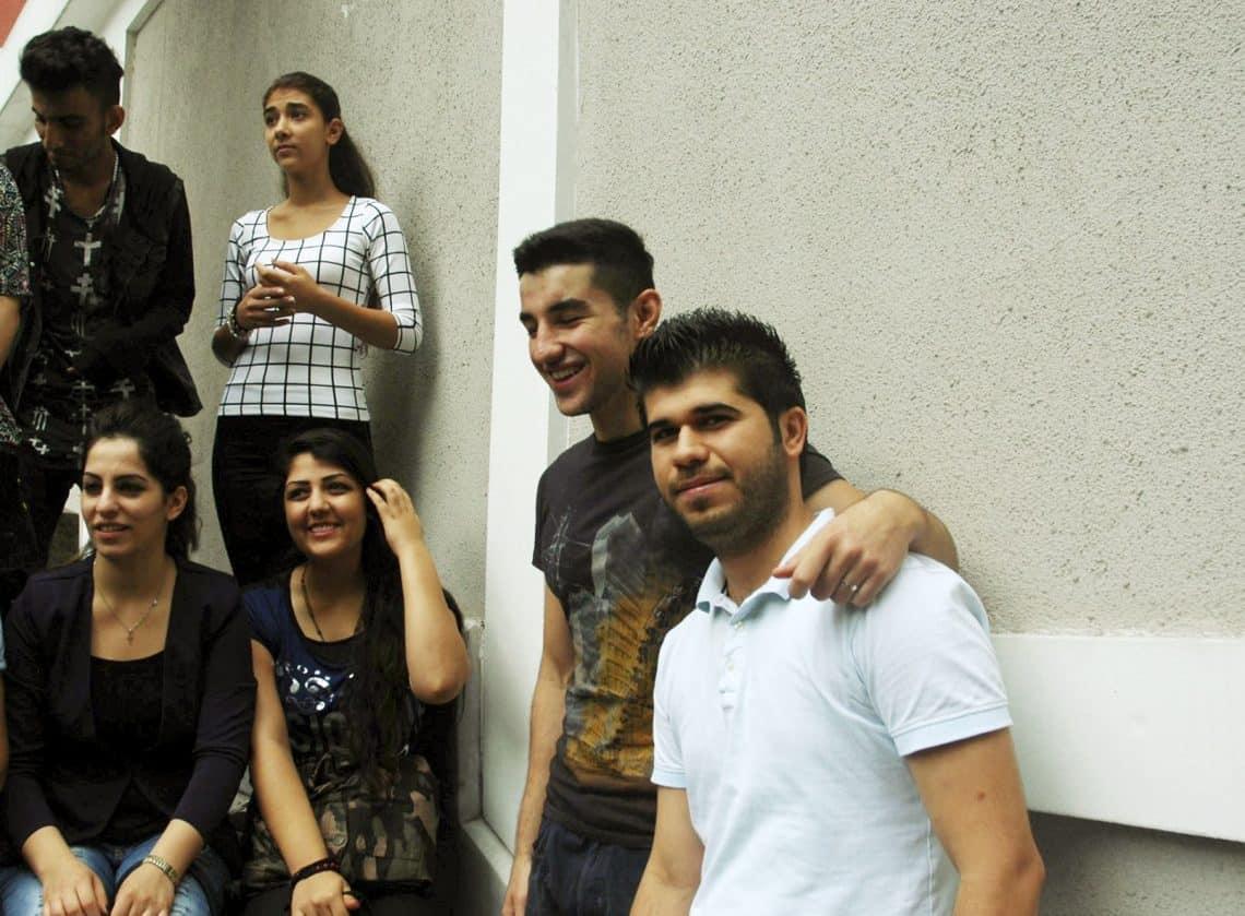 Fadi (à droite) entouré de jeunes réfugiés de l'aumônerie. © Anne-Laure Gatin