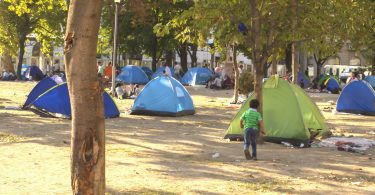 Un jeune garçon syrien, dans un camp de fortune près d'une station d'autobus à Belgrade, Serbie (Fotolia)