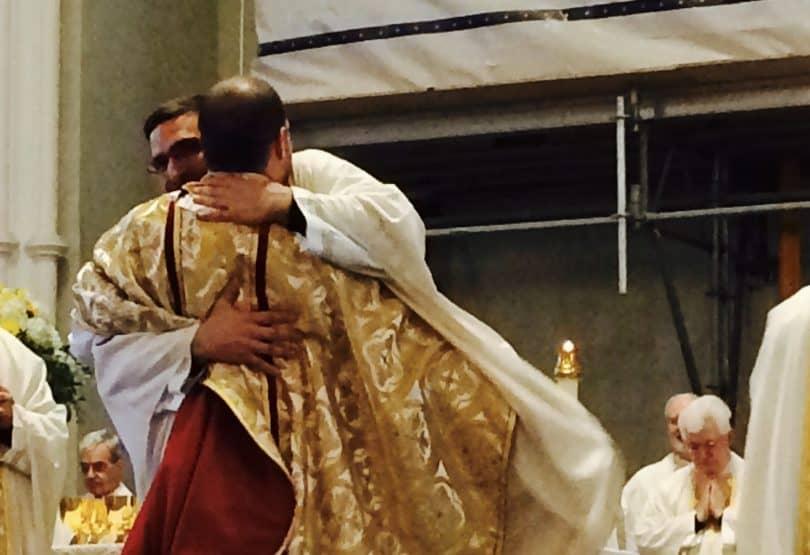 L'abbé Julien Malenfant (de dos), recevant l'accolade de son frère ainé et confrère, l'abbé Thomas.